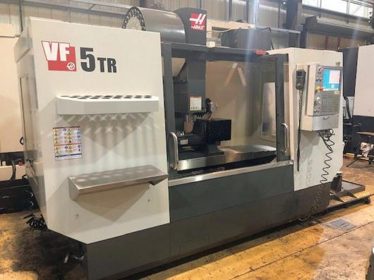 HAAS VF-5TR 5-Axis Vertical Machining Centre (2012) with HAAS Control, Traverses X Y Z 1270 x 660 x 635mm, A Axis -/+ 120 degrees, B Axis 360 degrees, Spindle Taper BT40, Spindle Speed 10000rpm, Motor 22Kw, Table size 210mm diameter, Programmable Coolant Nozzle, Swarf Auger, Tool Setter. S/No. 109511. Country of Origin: U.S.A.