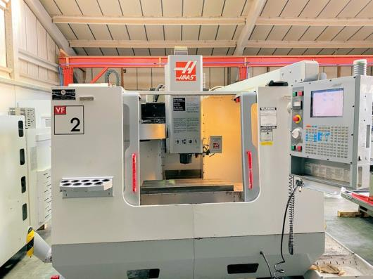 HAAS VF-2 Vertical Machining Centre (2003) with HAAS Control, Traverses X Y Z: 762 x 406 x 508, Table 914 x 356, Spindle Speed 0 - 7500rpm, Spindle Taper BT40, Spindle Motor 20Hp, 20 Station ATC, Programmable Coolant Nozzle, Low Volt light, 4th Axis Interface. S/No. 31615. Country of Origin: U.S.A.